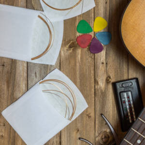 acoustic guitar and its accessories, strings, picks, capo, and tuner on wooden background